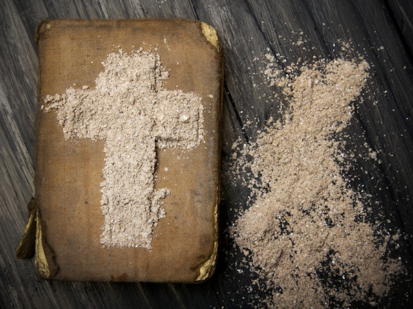 Old Bible and Cross of ash - symbols of Ash Wednesday.